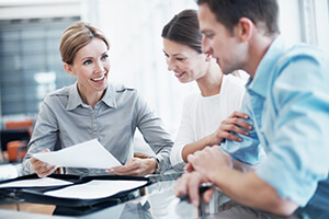 plan advisor talking with a man and woman reviewing paperwork